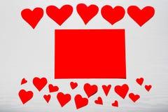 Fondo blanco de madera con los corazones rojos y el papel rojo de la hoja E Imagenes de archivo