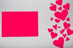 Fondo blanco de madera con los corazones rojos y el papel rojo de la hoja E Fotografía de archivo