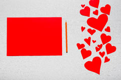 Fondo blanco de madera con los corazones rojos y el papel rojo de la hoja E Foto de archivo