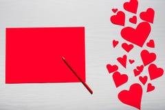 Fondo blanco de madera con los corazones rojos y el papel rojo de la hoja E Fotos de archivo libres de regalías