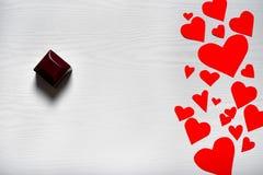 Fondo blanco de madera con los corazones rojos y una caja con una boda Fotografía de archivo libre de regalías