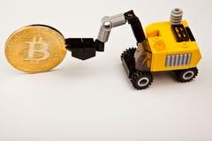 Fondo blanco del excavador del juguete de la moneda amarilla del bitcoin foto de archivo
