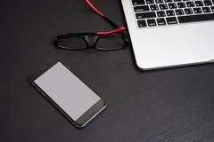 Fondo blanco del teléfono móvil con el teclado y las lentes del ordenador portátil imagen de archivo libre de regalías