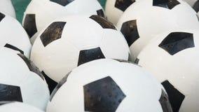 Fondo blanco y negro de muchos balones de fútbol Bolas del fútbol que nadan en un cierre puro del agua para arriba metrajes