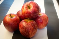 Fondo blanco y negro rayado Manzanas rojas en fondo blanco y negro rayado Endecha plana, visi?n superior, espacio para el texto foto de archivo