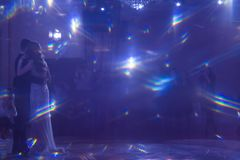 Fondo blu astratto Il bello abbagliamento magico ha rifranto la luce, quando una giovane coppia sta stando davanti ai fotografi c fotografia stock libera da diritti