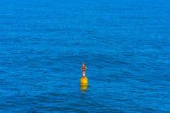 Fondo blu del mare con la boa gialla, struttura regolare in tonalità luminose del blu, Albania immagine stock libera da diritti