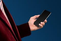 Fondo blu disponibile dello smartphone della tenuta dell'uomo d'affari fotografia stock