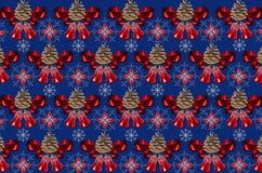 Fondo blu scuro eterogeneo con le campane, le pigne e gli archi di rosso Immagine Stock