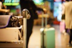 Fondo borroso: bolso del cubo y carretilla del aeropuerto en el aeropuerto Imágenes de archivo libres de regalías