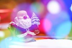 Fondo borroso con el juguete de Papá Noel y la iluminación colorida Fotografía de archivo libre de regalías
