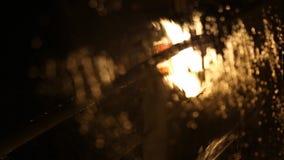Fondo borroso de la lluvia en la noche en la ventana almacen de metraje de vídeo