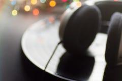 Fondo borroso de la música Auriculares que mienten en las luces multicoloras de Bokeh del fondo del negro del expediente de disco fotos de archivo
