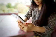 Fondo borroso de la mano de la chica joven que sostiene el teléfono móvil Imagen de archivo