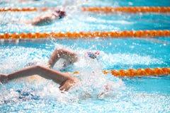 Fondo borroso del agua del descenso del chapoteo en la raza de la natación Imagen de archivo