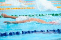 Fondo borroso del agua del descenso del chapoteo en la raza de la natación con swi Fotos de archivo libres de regalías