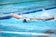 Fondo borroso del agua del descenso del chapoteo en la raza de la natación con swi Imagen de archivo