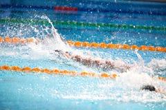 Fondo borroso del agua del descenso del chapoteo en la raza de la natación con swi Imágenes de archivo libres de regalías