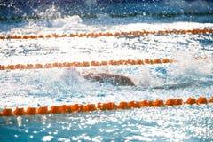 Fondo borroso del agua del descenso del chapoteo en la raza de la natación con swi Imagen de archivo libre de regalías