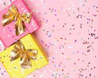 Fondo celebratorio con i contenitori ed i coriandoli di regalo di colore Fotografie Stock Libere da Diritti