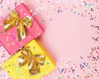 Fondo celebratorio con i contenitori ed i coriandoli di regalo di colore Fotografia Stock Libera da Diritti
