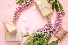 Fondo celebratorio con i fiori del lupino, i contenitori di regalo e la decorazione Immagine Stock Libera da Diritti