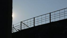 Fondo Cerca del metal en la parte de atrás del sol Movimiento de la cámara Los rayos de Sun iluminan la cerca almacen de video