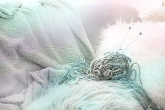 Fondo colorato nei colori morbidi filo per tricottare con i ferri da maglia Sul sofà nel salone accogliente Indicatore luminoso d fotografia stock libera da diritti