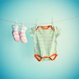 Fondo colorido para el bebé con dos calcetines rosados y el traje del cuerpo con el espacio de la copia Fotografía de archivo