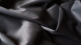 Fondo compuesto sedoso negro de la textura de las curvas de la tela del paño Fotografía de archivo libre de regalías