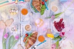 Fondo con diversos colores Un desayuno de la familia de cruasanes con el cohete y queso y café aromático, huevos de diferente Foto de archivo libre de regalías
