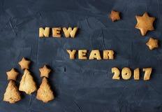 Fondo con el Año Nuevo cocido 2017 de las palabras del pan de jengibre con asteroide y el árbol de navidad - galletas formadas cr Imágenes de archivo libres de regalías