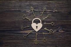 Fondo con el cerradura-corazón decorativo y llaves antiguas en de madera Imagen de archivo libre de regalías
