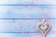 Fondo con el corazón decorativo y los pétalos rosados en la madera azul Foto de archivo