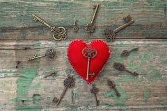 Fondo con el corazón rojo y llaves antiguas en viejo pintado de madera Fotos de archivo