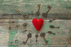 Fondo con el corazón rojo y llaves antiguas en viejo pintado de madera Fotografía de archivo libre de regalías