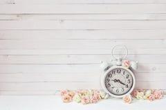 Fondo con el despertador blanco y las pequeñas rosas rosadas en blanco Fotografía de archivo