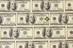 Fondo con el trébol de cuatro hojas hecho de cientos billetes de banco del dólar Foto de archivo