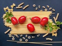 Fondo con espaguetis, tomates y verdes en un backgro oscuro Imagen de archivo libre de regalías