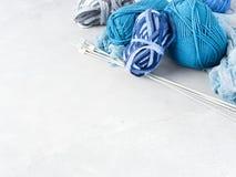 Fondo con hilado azul y agujas que hacen punto Fotografía de archivo libre de regalías