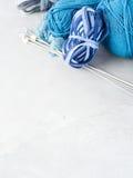 Fondo con hilado azul y agujas que hacen punto vertical Imagenes de archivo