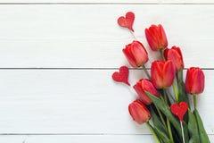 Fondo con il mazzo dei tulipani rossi e dei cuori decorativi su w Fotografie Stock