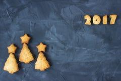Fondo con il pan di zenzero al forno sotto forma degli alberi di Natale e del testo 2017 Idea creativa Fotografie Stock