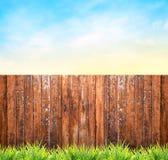 Fondo con il recinto, l'erba ed il cielo blu di legno immagini stock
