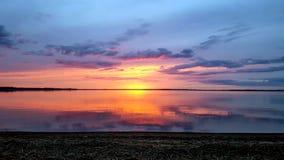 Fondo con il sole rosa ultra porpora di tramonto dell'estratto ed il cielo nuvoloso che riflettono in acqua del lago Razna, Letto fotografia stock libera da diritti