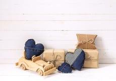 Fondo con l'automobile del giocattolo, i contenitori di regalo ed i cuori di legno del denim Fotografia Stock Libera da Diritti