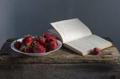 Fondo con la fresa y los libros rojos en la tabla Fotografía de archivo libre de regalías