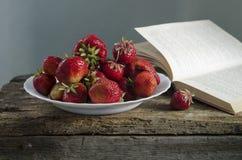 Fondo con la fresa y los libros rojos en la tabla Foto de archivo libre de regalías