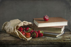 Fondo con la fresa y los libros rojos en la tabla Imágenes de archivo libres de regalías
