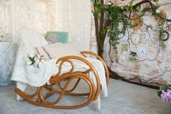 Fondo con la sedia di oscillazione con i cuscini sui precedenti dei rami con i fiori e gli orologi di parete fotografia stock